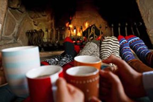 Hands holding cocoa cups in front of a fireplace.