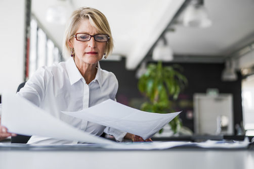 Woman wearing glasses looking at papers